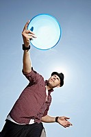 Germany, Cologne, Mature man playing flying disc