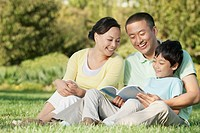 Chinese family relaxing in park reading book