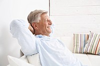 Spain, Senior man relaxing on couch, smiling