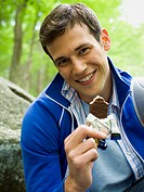 Close_up of a young man eating a chocolate bar