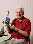 Portrait of a senior man holding a trophy
