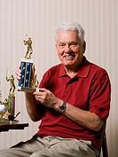 Portrait of a senior man holding a trophy