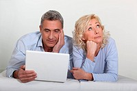 Middle aged couple with a laptop on their bed.