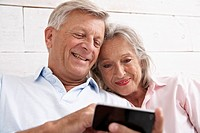 Spain, Senior couple using mobile phone, smiling