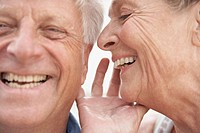 Spain, Senior woman whispering into ear of man, smiling (thumbnail)