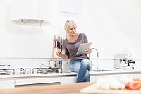 Germany, Bavaria, Munich, Woman watching digital tablet and preparing food