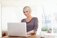 Germany, Bavaria, Munich, Woman using laptop, smiling