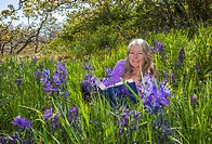 A senior woman reads in a sea of camassia, victoria british columbia canada