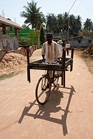 Man cycling through village street with two metal bed frames balanced on his bicycle, Hirapur, Orissa, India, Asia