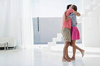 Spain, Mid adult couple embracing in modern apartment