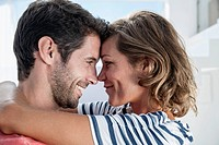 Spain, Mid adult couple embracing each other in modern apartment