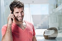 Spain, Mid adult man talking on cell phone, smiling