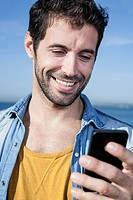 Spain, Mid adult man using smart phone, smiling