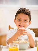 Young boy smiling and eating breakfast cereal