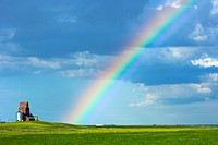 Rainbow in the sky beside a grain elevator, saskatchewan canada