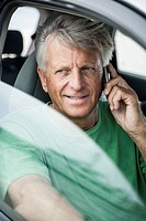 Spain, Senior man sitting in car and talking on phone