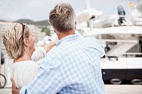 Spain, Senior couple pointing to boat at harbour
