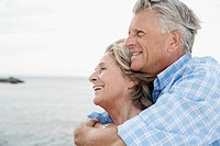 Spain, Senior couple embracing at harbour, smiling (thumbnail)