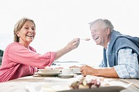 Spain, Senior couple having lunch, smiling