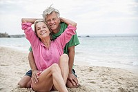 Spain, Seniors couple sitting on beach