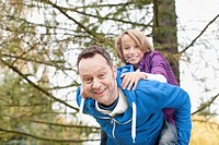 Germany, Leipzig, Father giving piggyback ride to son, smiling