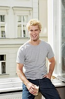 Germany, Berlin, Young man sitting at open window, smiling