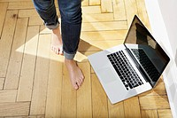 Germany, Berlin, Young woman feets walking by laptop