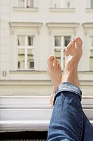 Germany, Berlin, Young woman feets on open window