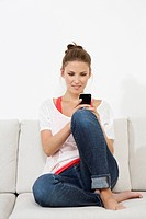 Germany, Berlin, Young woman sitting on couch and using smart phone