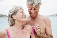Spain, Senior couple undressing on beach