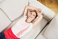 Germany, Berlin, Young woman lying on couch, smiling