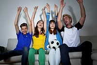 Germany, Berlin, Group of young people sitting on couch in front of screen watching sports event