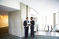 Two businessmen talking at top of escalator