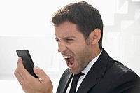 Spain, Businessman shouting on mobile phone