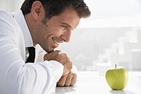 Spain, Businessman looking at apple, smiling
