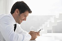 Spain, Businessman using mobile phone, smiling
