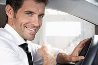 Spain, Businessman sitting in car, smiling, portrait