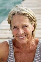 Spain, Senior woman sitting on jetty at the sea, smiling, portrait