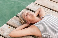 Spain, Senior woman relaxing on jetty at the sea