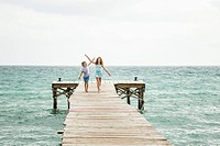 Spain, Girl and boy running on jetty at the sea