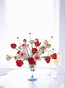 Red and pink ranunculus arrangement on table