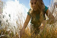 woman standing in beach grass, looking for sth