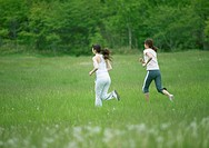 Young women running on the grass