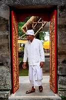 A Hindu priest entering a Temple through an ornately decorated door  Pura Dalem Tengaling Temple at Pejeng  Near Ubud, Bali, Indonesia