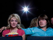 Boy reaching arm out behind girl with popcorn at movie theater