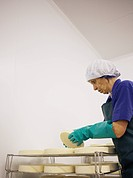 dairy emplyee turning maturing organic cheeses on