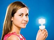 Woman holding energy efficient lightbulb smiling