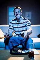 Man on sofa with frozen dinner and napkin with food smiling