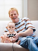 Man and baby on sofa with video game controller smiling