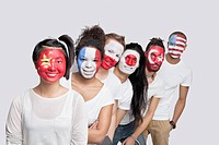 Portrait of Multi_ethnic group of friends with various national flags painted on their faces standing in queue against white background